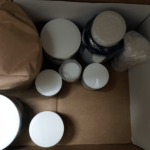 Various nootropic jars in a shipment package with one jar being wrapped in brown paper